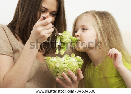 little girl eats vegetarian meal with the young mother #94634530