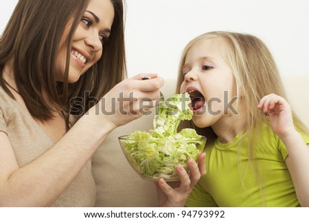 little girl eats vegetarian meal with the young mother #94793992