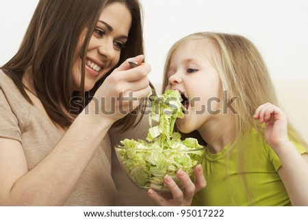 little girl eats vegetarian meal with young mother #95017222