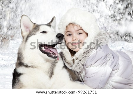 Little girl embrace five month old malamute puppy