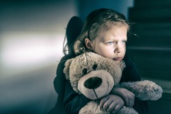 Little girl embracing her teddy bear - feels lonely -  if you are small sad girl teddy bear is willing to be your best friend - instagram filter applied