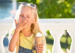 Little girl enjoy ice cream in a vaiel glass. Teen is fashionably dressed. Child posing against the backdrop of street scenery