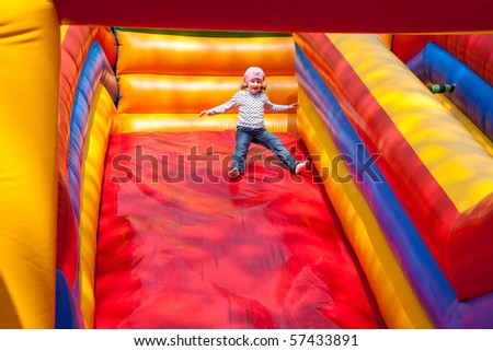Little girl enjoying a big red blown up colorful slide.