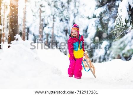 little girl enjoying a sleigh ride child sledding toddler kid riding a sledge - Christmas Vacation Sled