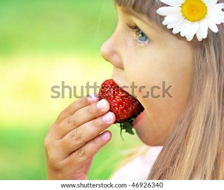 Little girl enjoying eating strawberry