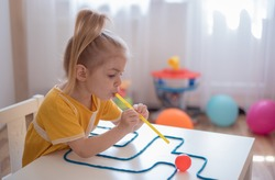 Little girl enjoying game playdough straw maze. Great activity for building oral motor skills at home.