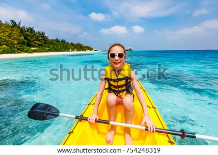 Little girl enjoying paddling in kayak at tropical ocean water during summer vacation