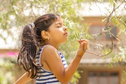 Little girl enjoying the smell of plants in nature