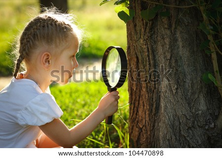 Little girl examining the tree stem through the magnifying glass outdoors