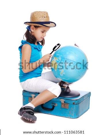 Little girl exploring a globe  with a magnifying glass sitting on a blue suitcase