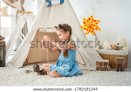 Little girl exploring jewellery from small chest sitting on room's floor in front of wigwam Сток-фото ©