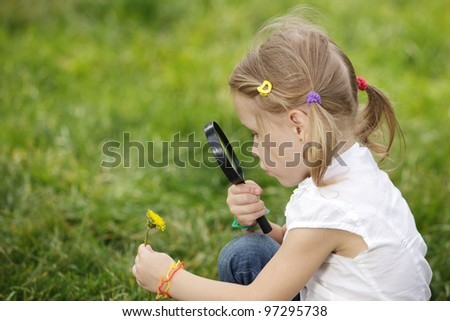 Little girl exploring the flower through the magnifying glass outdoors