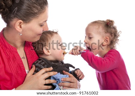 little girl feeding her baby brother