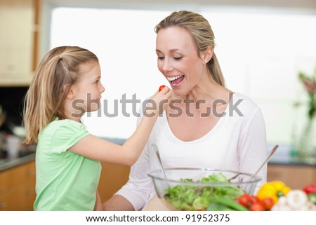 Little girl feeding her mother with tomato