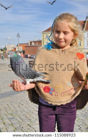 Little girl feeds doves in the city.