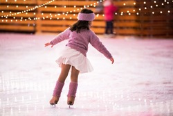 Little girl figure skater in a pink sweater is skating on a winter evening at an outdoor ice rink, back view