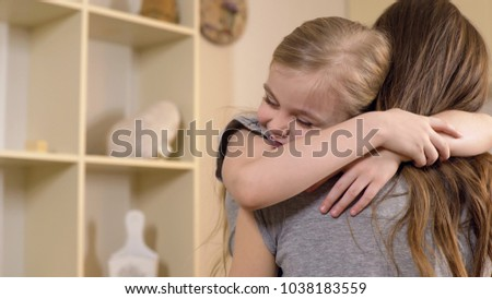 Little girl firmly and with love hugging her mother, warm relations, childhood