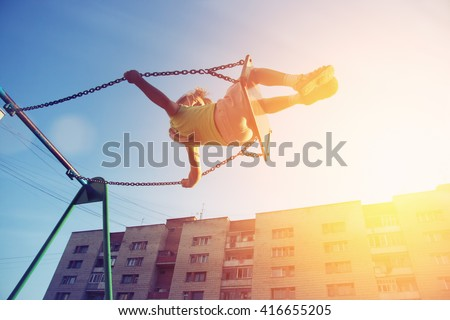 Little girl flying on swing in city house yard. Childhood, Freedom, Happy, Summer Outdoor