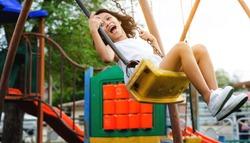 Little girl flying on swing. She is freedom