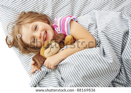 little girl four years old in the bed with toy