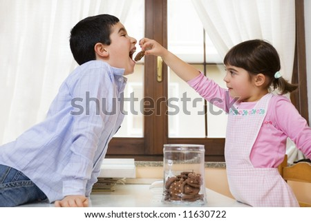 little girl giving a cookie to her brother in the kitchen