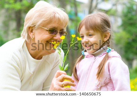 little girl giving her great grandmother yellow flowers