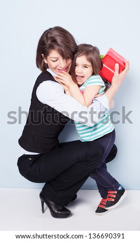little girl giving her mom a present on blue background