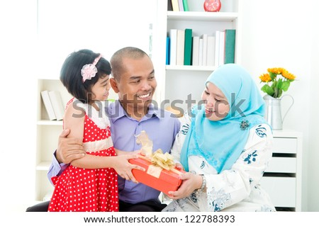 little girl giving present to her mother