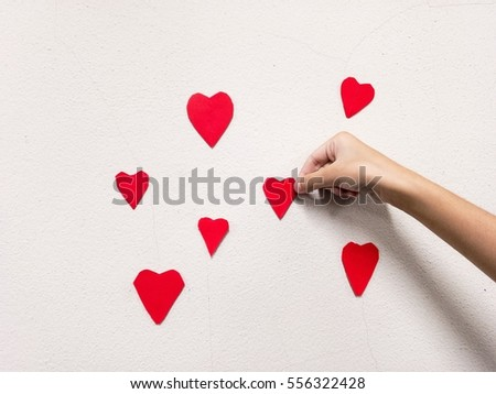 little girl hand stick Red heart shaped on white wall background. Symbol of love on the wall.home decor for valentines day and lovely special occasions to beloved copy space #556322428