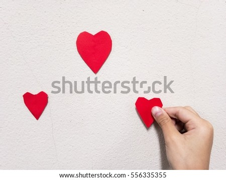 little girl hand stick Red heart shaped on white wall background. Symbol of love on the wall.home decor for valentines day and lovely special occasions to beloved copy space #556335355