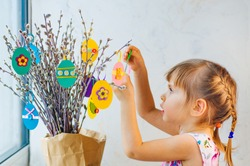 Little girl hanging Easter eggs cutted from color paper decorated with ribbon and buttons on willow branches. Idea for DIY decoration with children.