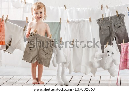 Little girl hangs laundry or toys in the laundry