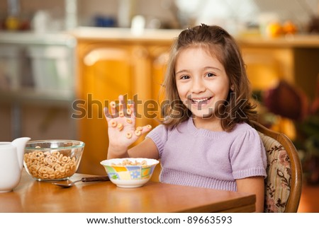 little girl having breakfast: laughing at sticky cereals on her hand