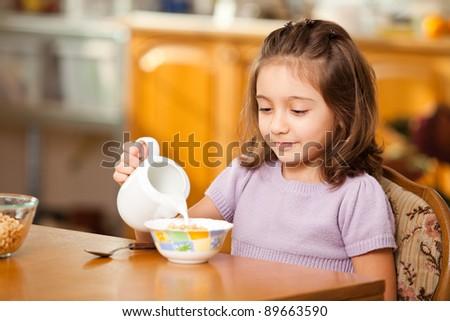 little girl having breakfast:pouring milk in the bowl