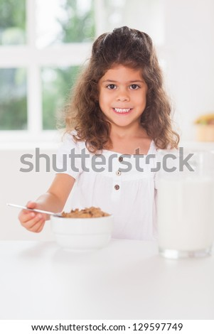 Little girl having cereal for breakfast