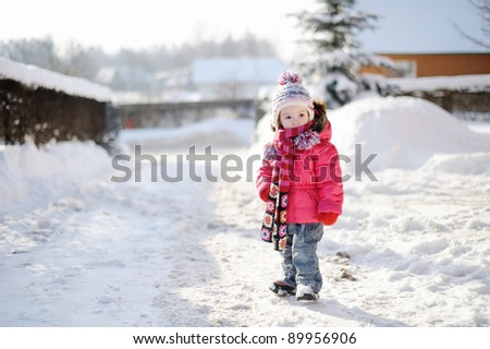 Little girl having fun at winter day