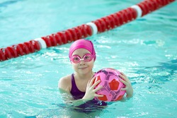 Little girl having fun learning to swim with a ball in a swimming pool.Joyful smiling girl swimmer in a cap and goggles learns professional swimming