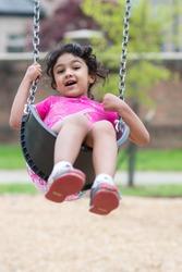Little Girl Having Fun on a Swing in a Park