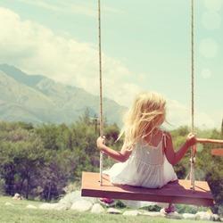 Little girl having fun on a swing outdoor