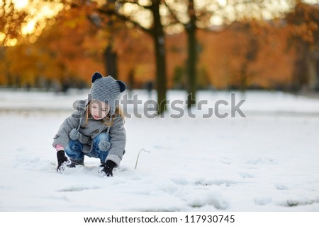 Little girl having fun on winter day in city