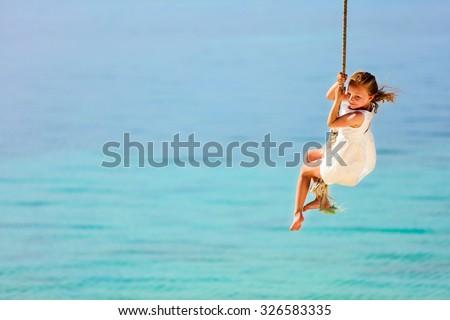 Little girl having fun swinging on a rope at tropical island beach