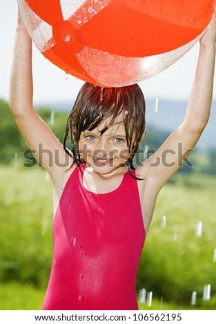 little girl having fun with ball and rain of water drops