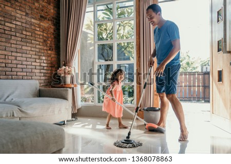 little girl help her daddy to do chores at home #1368078863
