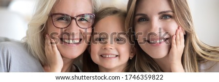 Little girl her young mother and mature grandma portrait. Multi generational women faces smiling looking at camera close up view photo, family bond concept. Horizontal banner for website header design