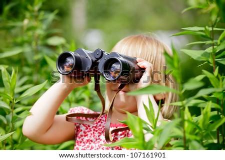 Little girl hiding in grass looking through binoculars outdoor