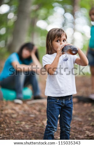 Little girl hiker drinks a cold tea from bottle while resting. Family on background
