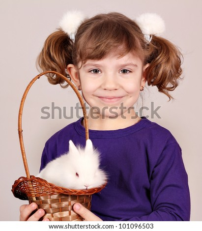 little girl holding a basket with dwarf white bunny