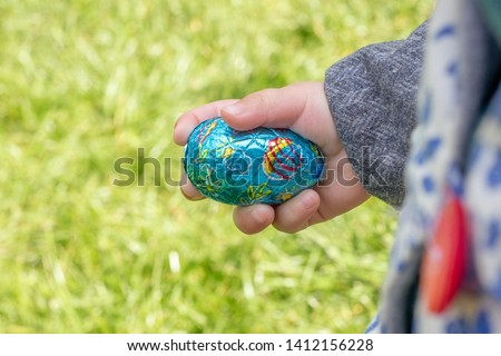 Little girl holding a blue chocolate easter egg #1412156228