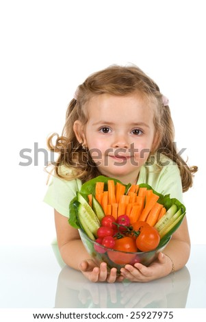 Little girl holding a bowl of vegetables leaning on the table - isolated
