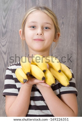 little girl holding a bunch of bananas on the background of wooden boards